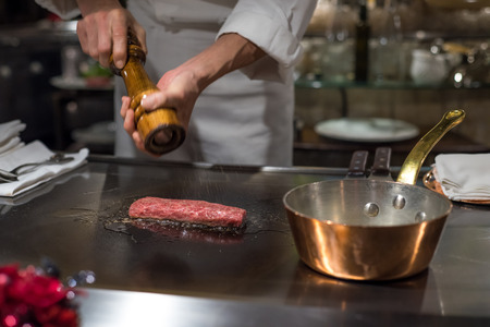 chef kitchen: Chef cooking wagyu beef in Japanese teppanyaki restaurant, Tokyo, very shallow focus Stock Photo