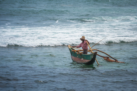 outrigger: KOATTAGODA, SRI LANKA - February, 11, 2016: Sinhalese fishermen in traditional outrigger canoe