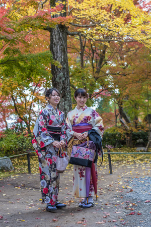 momiji: KYOTO, JAPAN - November, 18, 2014: Two japanese girls in traditional kimono, momiji season in Kyoto