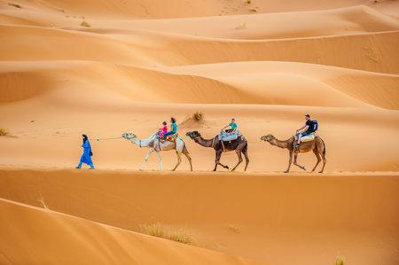 erg: ERG CHEBBY, MOROCCO - April, 12, 2013: Tourists riding camels in Erg Chebbi, Morocco