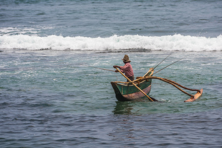KOATTAGODA, SRI LANKA - February, 11, 2016: Sinhalese fishermen in traditional outrigger canoe