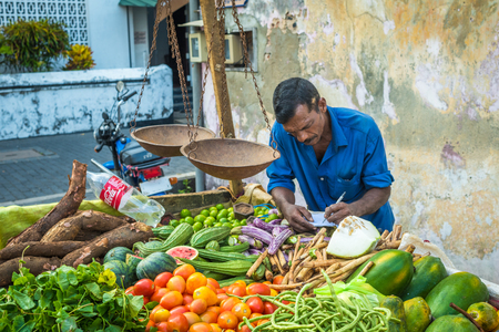 galle: GALLE, SRI LANKA - February, 14, 2016: Street vendor with vegetables and vintage scales