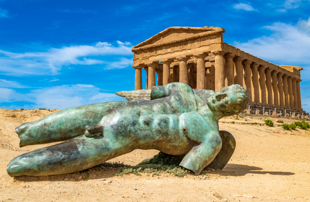 Temple of Concordia and the statue of Fallen Icarus, in the Valley of the Temples, Agrigento, Sicily, Italy 免版税图像