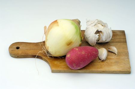 potato, garlic, onion on a wooden cooking plate photo