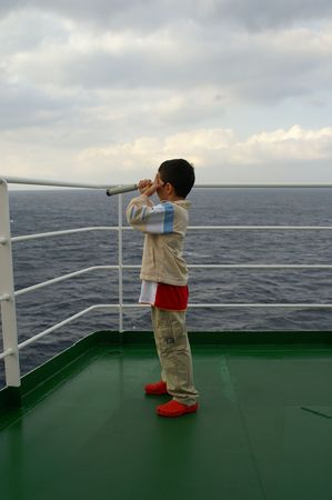 romantics: A child boy on deck of cruise ship looks to a glass to ships in a Mediterranean port - romantics Stock Photo