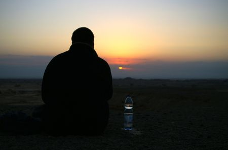 romantics: Looking to a sunset - person with a bottle of water
