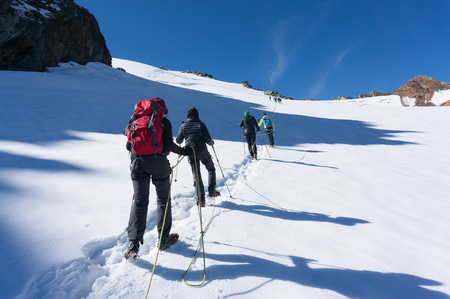 Hiking to mountain summit on snow glacier extreme trek