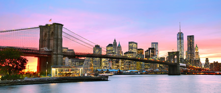 Panoramic view of Manhattan and Brooklyn Bridge at dusk.