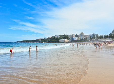 summer vacation bikini: Swimmers relaxing on the beach in summer at Coogee Beach, Sydney, Australia Editorial