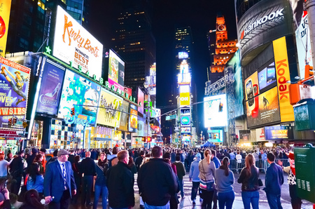 Times Square with lots of visitors at night in New York City