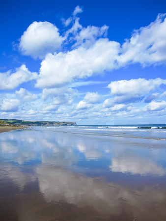 whitby: Reflection of blue sky on the beach in a sunny day