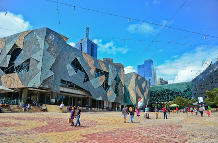 Melbourne, Australia - January 18, 2015: People visit Federation Square in Melbourne city cetre on January 18, 2015. The square is a public space created in 2002 in the heart of Melbourne.