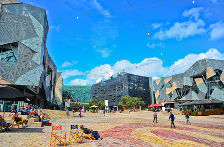 public space: Melbourne, Australia - January 18, 2015: People visit Federation Square in Melbourne city cetre on January 18, 2015. The square is a public space created in 2002 in the heart of Melbourne.