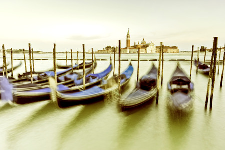 Gondolas moving along the wave on the Grand Canal in Venice at dusk. Stock Photo