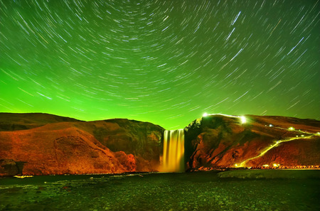 View of the northern light with star trails at Skogafoss in Iceland.