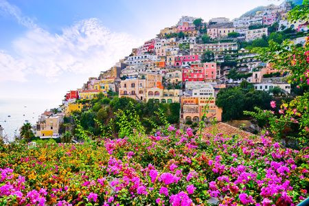 View of Positano village with purple flowers in summer in Italy. Stock Photo