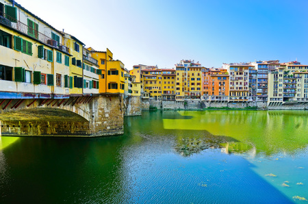 View of the Old Bridge across the Arno River in Florence on a sunny day