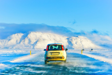 Car driving on the icy road from the plateau around the Thingvellir National Park in Iceland in winter