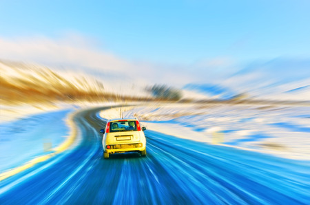 Car driving on the icy road in winter in Iceland with motion effect. Фото со стока