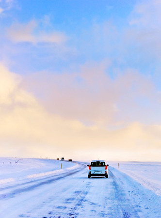 A car driving on the icy road from the plateau around the Thingvellir National Park in Iceland in winter.