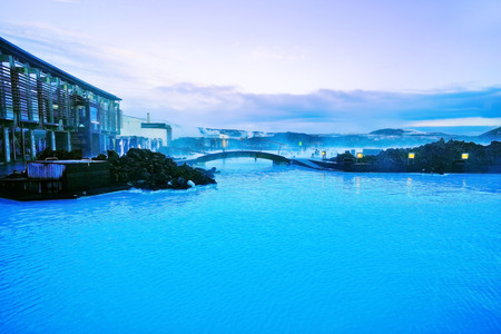 View of the Blue Lagoon pool and visitors building at dusk with lots of tourists bathing in Blue Lagoon, Iceland on January 27, 2017. Editorial