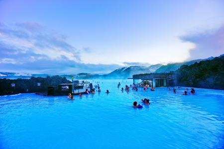 2017 년 1 월 27 일에 블루 라군, 아이슬란드에서 목욕하는 관광객이 많은 황혼의 블루 라군 수영장의 전망. 에디토리얼
