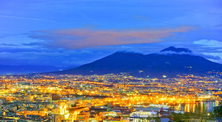 View of the city center of Naples and Mount Vesuvius along the Gulf of Naples at night in Naples, Italy. Redakční