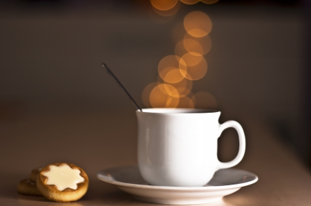 a cup of coffee with bubbles and a snack Stock Photo