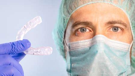 Dentist holding a transparent dental aligner with a light blue background
