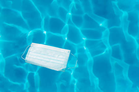 Close-up of a protective mask floating in the water of a swimming pool. Concept of hygiene and cleaning. Selective focus