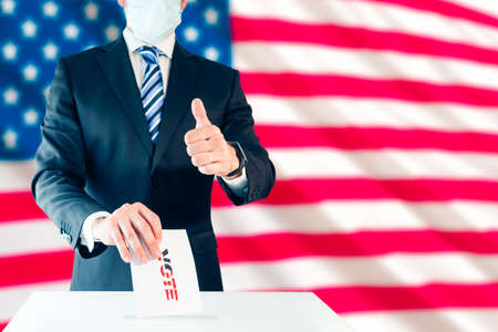 Elegant man in protective mask voting for US president and thumb up with the US flag behind him. Selective focus