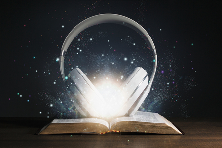 Headphones on the Holy Bible with glow coming out of the bible.