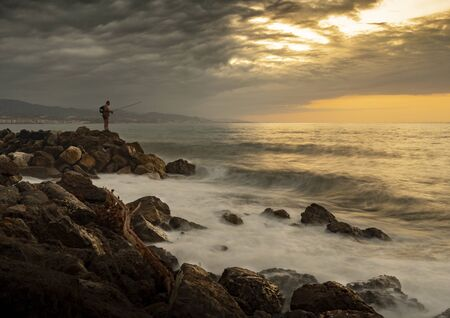 Fisherman on rocks fishing in front of the mediterranean sea at dawn orange