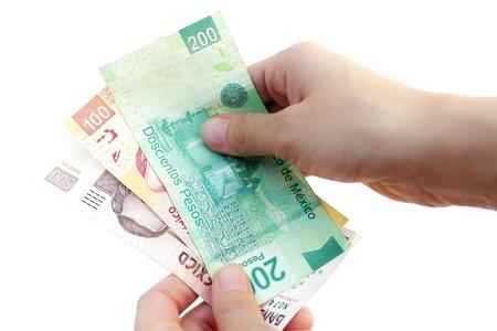 Hands counting Mexican Pesos bills