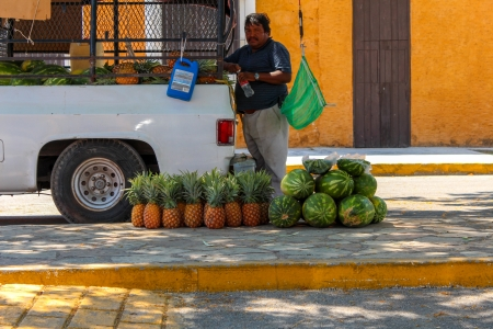 seller: Merida,Yucatan, Mexico - March 30, 2013: A Man Selling Watermelon and Papaya on the streets of a Yucatan small town or pueblo