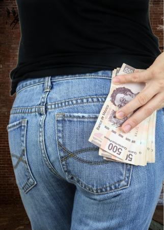 retrovisor: Retrovisor de una pila de dinero en el bolsillo trasero de una mujer Foto de archivo