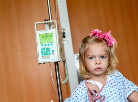 Recovering Little baby girl hospitalized with a Intravenous bag on a pole  Real situation photo