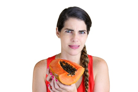 Young woman holding a rotten Papaya in disgust photo