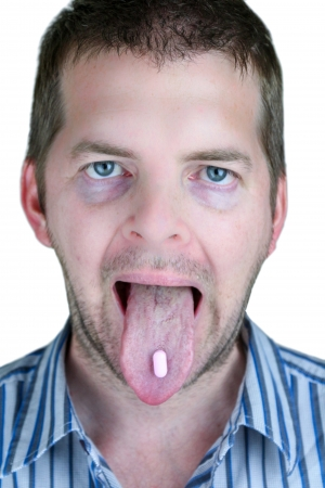 Sick Face young man with a pill on his tongue