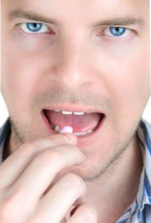 何か痛みを緩和する薬を服用して痛み若い男を容易にするため 写真素材