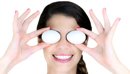 protein source: Young Woman holding a couple eggs over her eyes Stock Photo