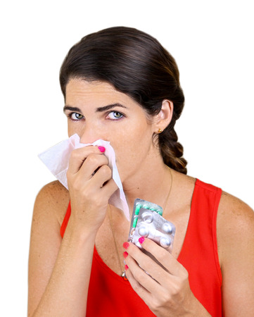 Closeup of beautiful Caucasian woman with cold sneezing into tissue photo