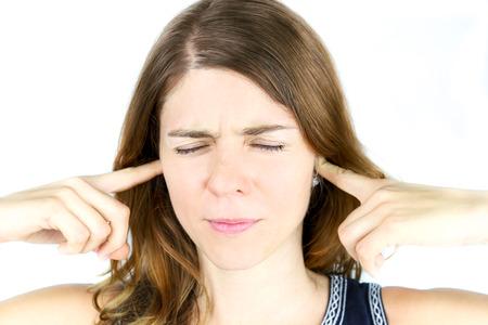 若い女性を刺激音を遮断する彼女の耳の上彼女の手を保持します。