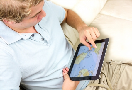デジタル タブレットを使用して、世界地図を見るするカジュアルな男