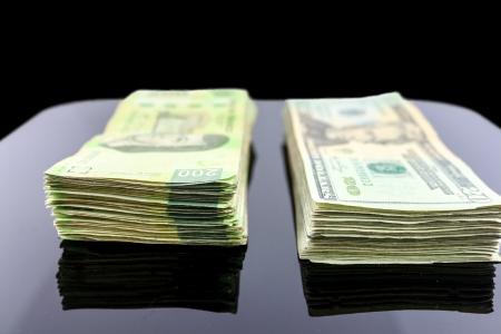 私たちのドル札の束と一緒にメキシコ ペソ紙幣の束