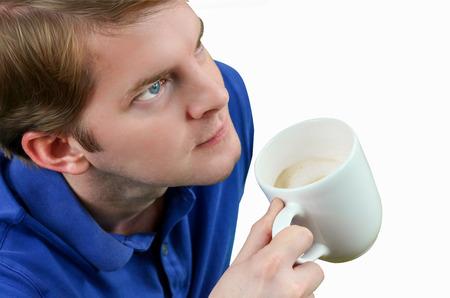 一杯のコーヒーを飲むカジュアルな若い男