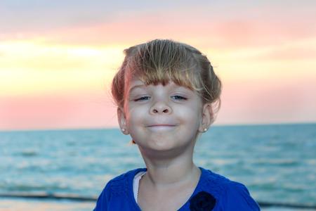 ビーチの背景に変な顔を作る少女の肖像画 写真素材