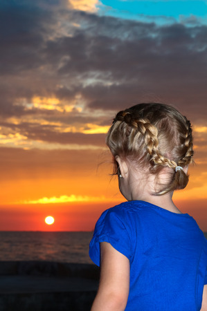 ユカタン半島のビーチで夏の夜を下る太陽を見ている少女