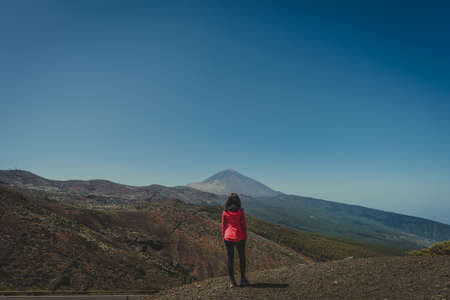 young woman looks to the horizon where a mountain is seen in the background