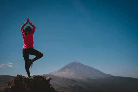 a young woman does yoga on top of a stone looking at a mountain in the background